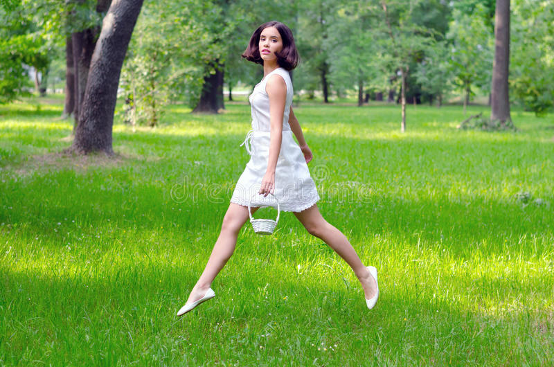 Beautiful girl with small white basket jumping high on spring meadow royalty free stock image