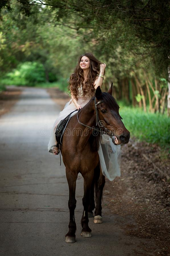 beautiful girl in a smart dress riding a horse laughing stock photography