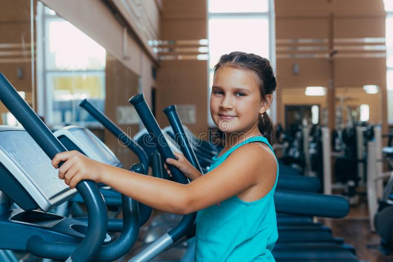 Beautiful girl with a smile runs on a trainer in the gym. Little beautiful girl with a smile runs on a trainer in the gym stock image