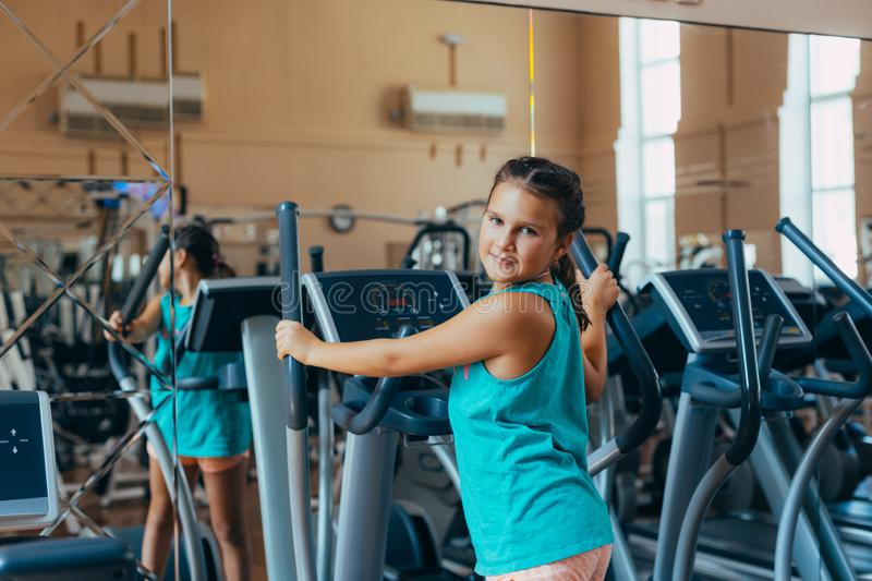 Beautiful girl with a smile runs on a trainer in the gym. Little beautiful girl with a smile runs on a trainer in the gym royalty free stock images