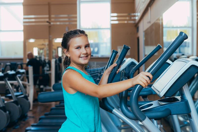 Beautiful girl with a smile runs on a trainer in the gym. Little beautiful girl with a smile runs on a trainer in the gym royalty free stock photos