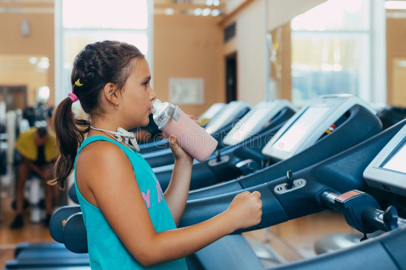 Beautiful girl with a smile runs on a trainer in the gym. Little beautiful girl with a smile runs on a trainer in the gym royalty free stock image