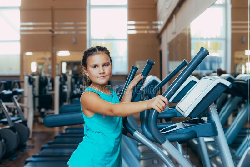 Beautiful girl with a smile runs on a trainer in the gym. Little beautiful girl with a smile runs on a trainer in the gym stock photo