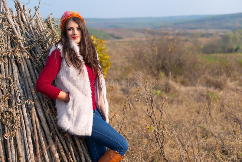 Beautiful girl smiling at the camera, in stylish fashion clothes in autumn scenery outdoors. Gorgeous romantic young stock image