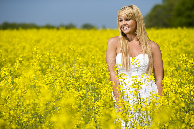Download A Beautiful Girl Smiling In A Field Of Yellow Flowers Stock Photo - Image: 30674782