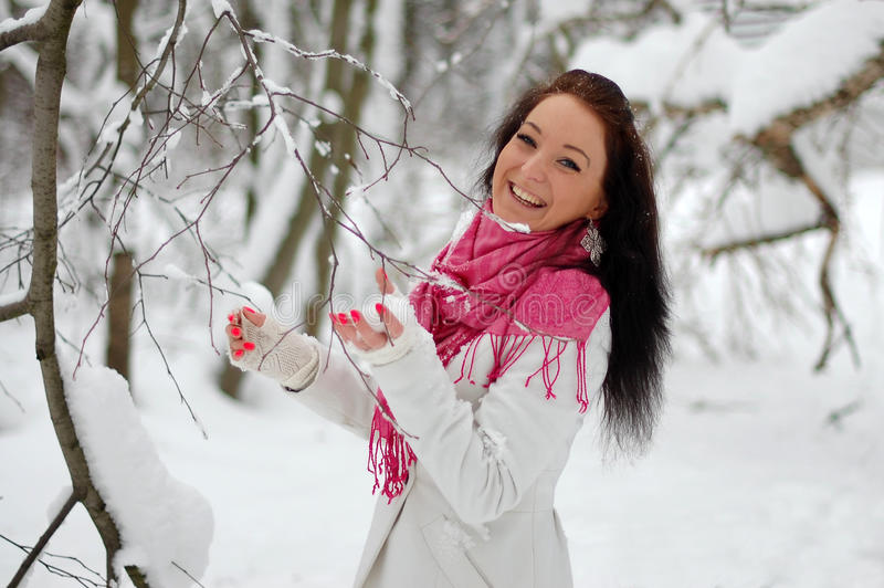 Beautiful girl smiling. Frost, winter. Beautiful brunette girl, holding a pink flower. Winter, snow, frost stock image