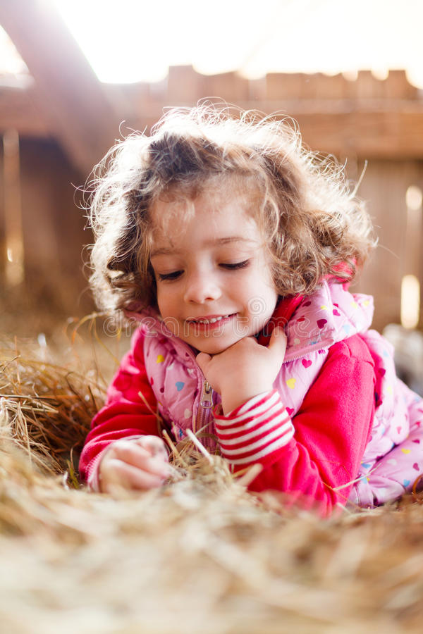 Beautiful Girl Smiling. Beautiful innocent little girl playing in hay smiling cutely stock photography