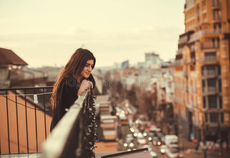 Beautiful girl smiling and looking down from rooftop over a city. Young woman thinking in urban area. Beautiful girl smiling and looking down from rooftop over a stock photos