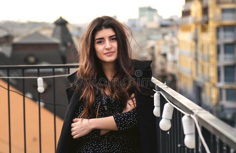 Beautiful girl smiling on rooftop over city. Young woman thinking in urban area. Beautiful girl smiling on rooftop over city. Young woman thinking about stock image