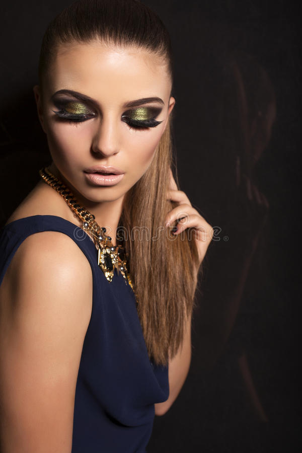 Beautiful girl with smokey eyes makeup and bijou. Studio fashion portrait of beautiful glamour model with smokey eyes makeup and jewellery stock photography