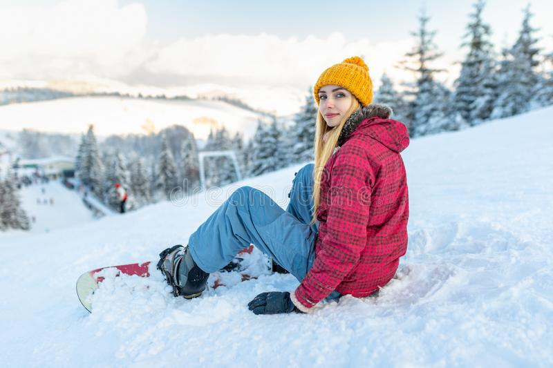Beautiful girl snowboarder sitting alone in the snow on hill mountain outdoor, winter sport activity royalty free stock images