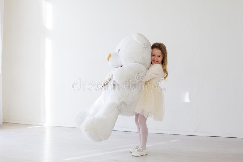 Beautiful girl with soft toy big bear. Beautiful girl with soft toy big polar bear stock image