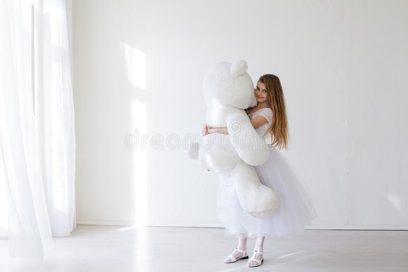 Beautiful girl with soft toy big bear. Beautiful girl with soft toy big polar bear stock photography