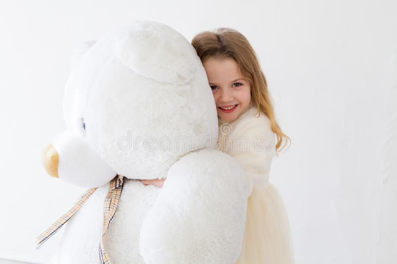 Beautiful girl with soft toy big bear. Beautiful girl with soft toy big polar bear royalty free stock photography