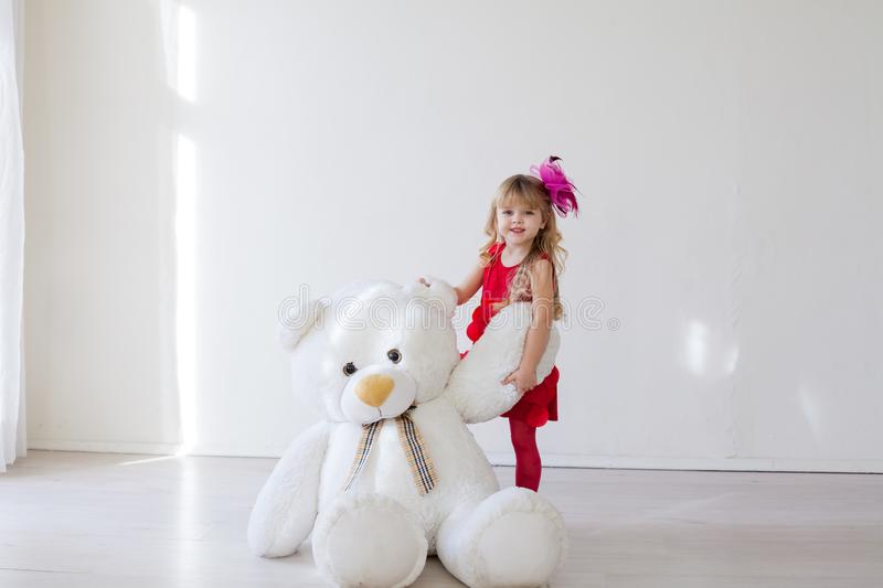 Beautiful girl with soft toy big bear. Beautiful girl with soft toy big polar bear stock images