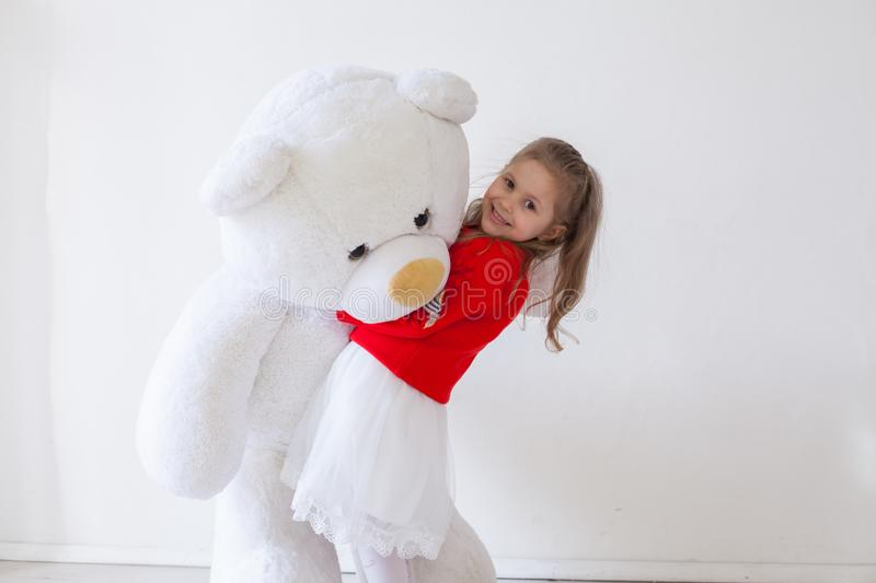Beautiful girl with soft toy big bear. Beautiful girl with soft toy big polar bear royalty free stock images