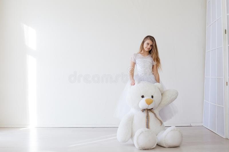 Beautiful girl with soft toy big bear. Beautiful girl with soft toy big polar bear royalty free stock photo