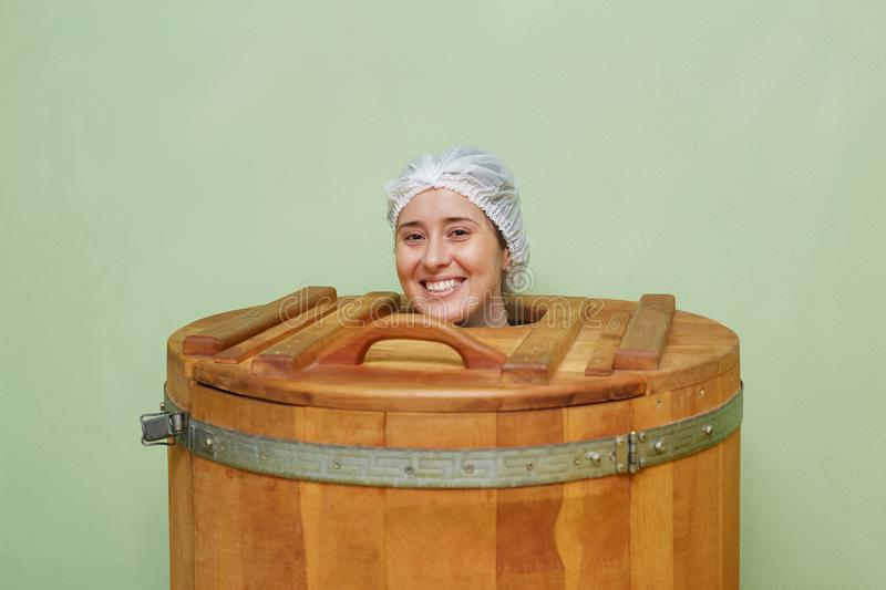 Beautiful girl in spa center. Phyto cedar barrel sauna royalty free stock photography
