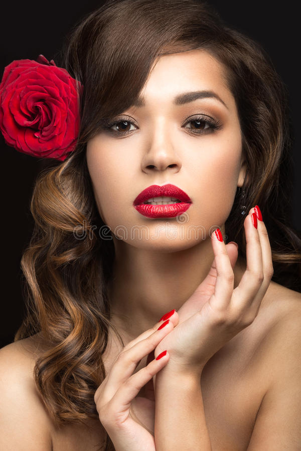 Beautiful girl in the Spanish way of Carmen with red lips and a rose in her hair. Picture taken in the studio on a black background. Beauty face royalty free stock images