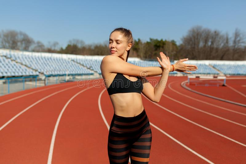 Beautiful girl in sportswear standing on the running track and preparing to run. Morning warm-up before exercise. Beautiful girl in sportswear standing on the royalty free stock images