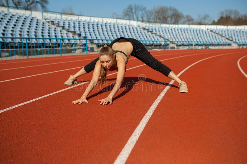Beautiful girl in sportswear standing on the running track and preparing to run. Morning warm-up before exercise. Beautiful girl in sportswear standing on the royalty free stock photos