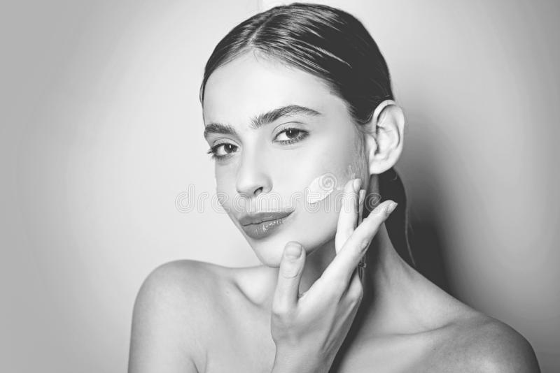 Beautiful girl spreading cream on her face. Skin cream concept. Facial care for female. Keep skin hydrated regularly royalty free stock photo