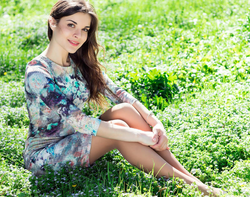 Beautiful girl in spring park. Beautiful young dreamy girl sitting on grass in spring park on sunny day and smiling stock images