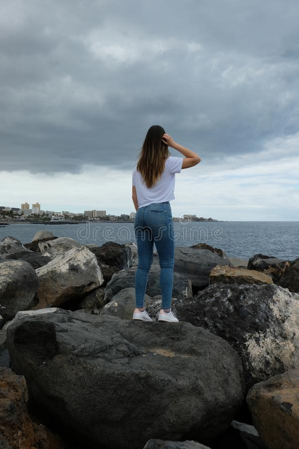 Beautiful girl standing on beach rocks looking to the sea royalty free stock image