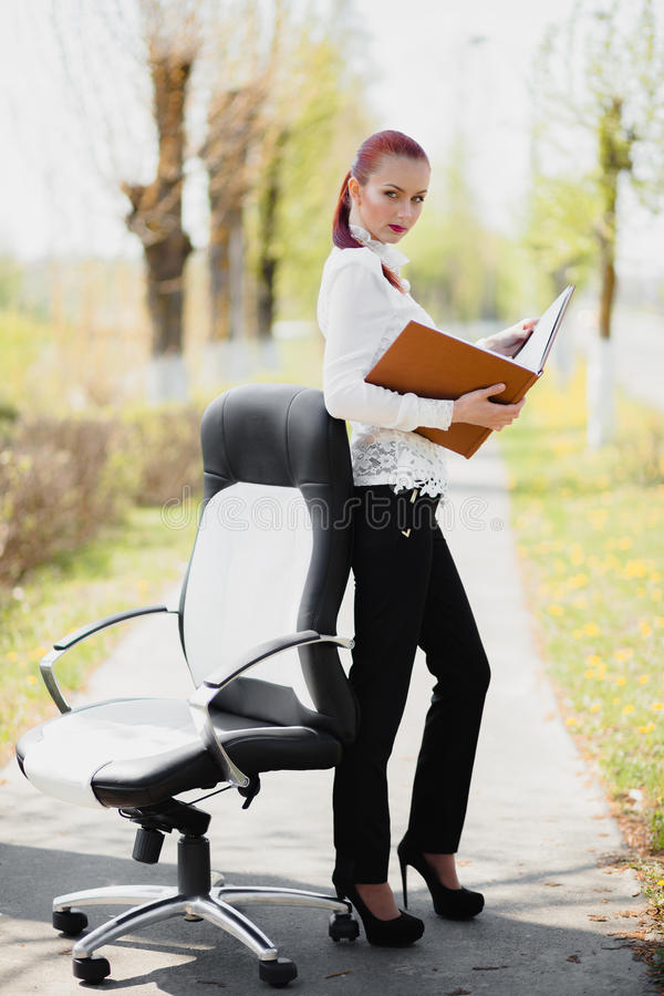 Beautiful girl standing at the chair stock photography