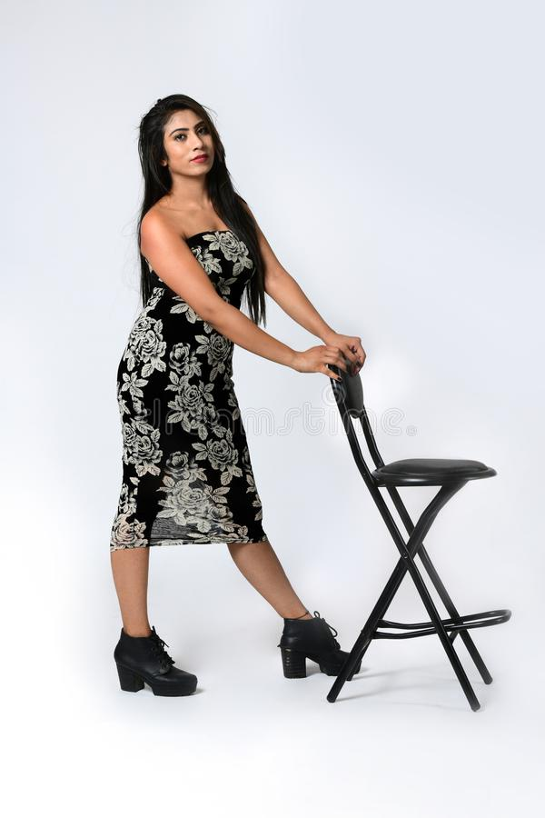 Beautiful girl is standing on the floor in style is holding chair royalty free stock images