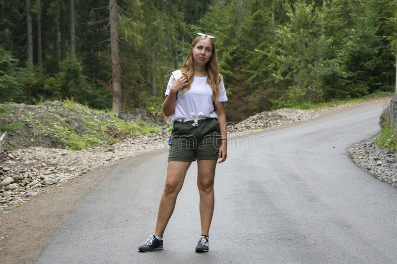 Beautiful girl is standing in the middle of a mountain road royalty free stock photos