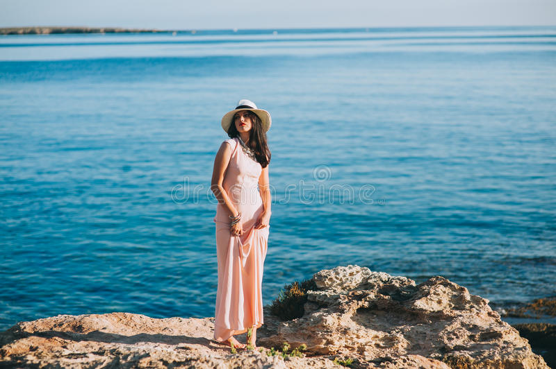 Beautiful girl standing on rocky outcrops seaside stock photo