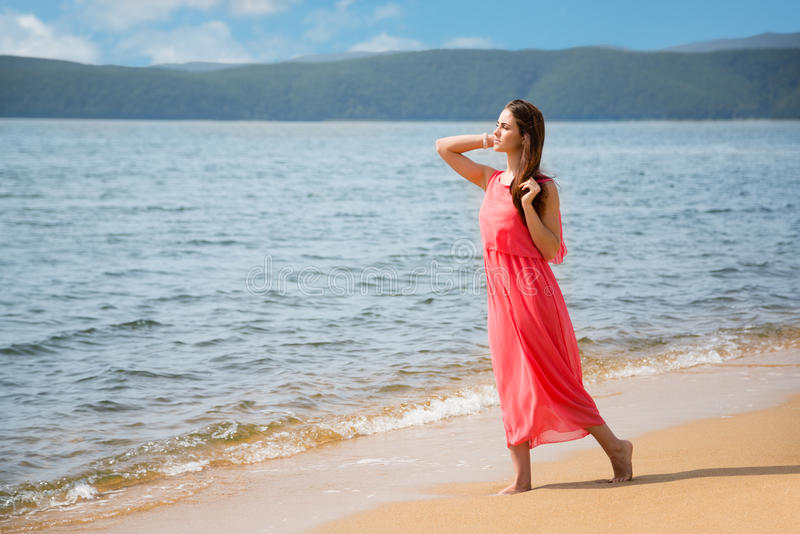 Beautiful girl standing on the sandy shore royalty free stock photos