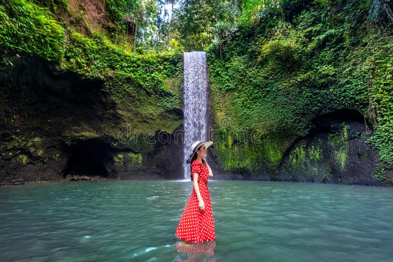 Beautiful girl standing in Tibumana waterfall in Bali, Indonesia. stock photo