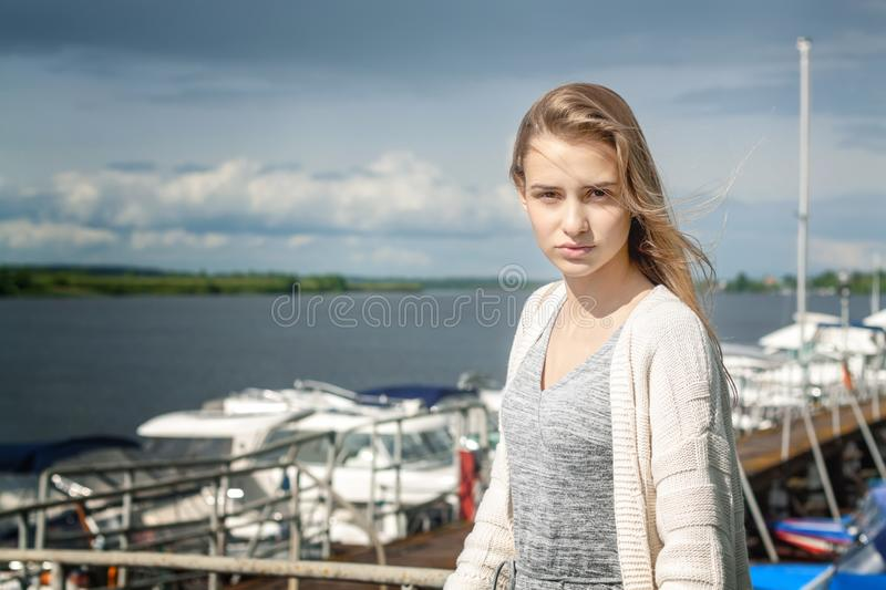 A beautiful girl stands alone on the pier against the background of the watery surface and thunderclouds extending beyond the hori. Zon. The wind spreads her royalty free stock image