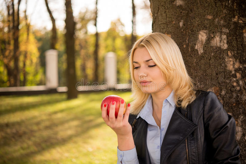 Beautiful girl stands near a tree and looking at an apple in her royalty free stock photos