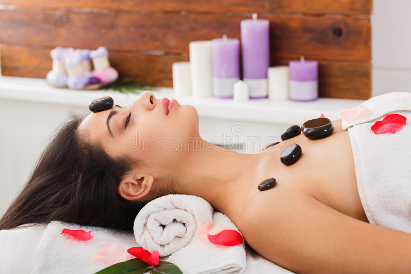 Beautiful girl at stone massage spa in wellness center. Black marble stone massage in ayurvedic spa. Beautiful girl in wellness center. Professional relaxation royalty free stock images