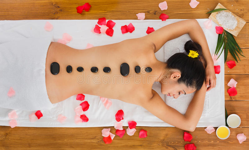 Beautiful girl at stone massage spa in wellness center royalty free stock photos