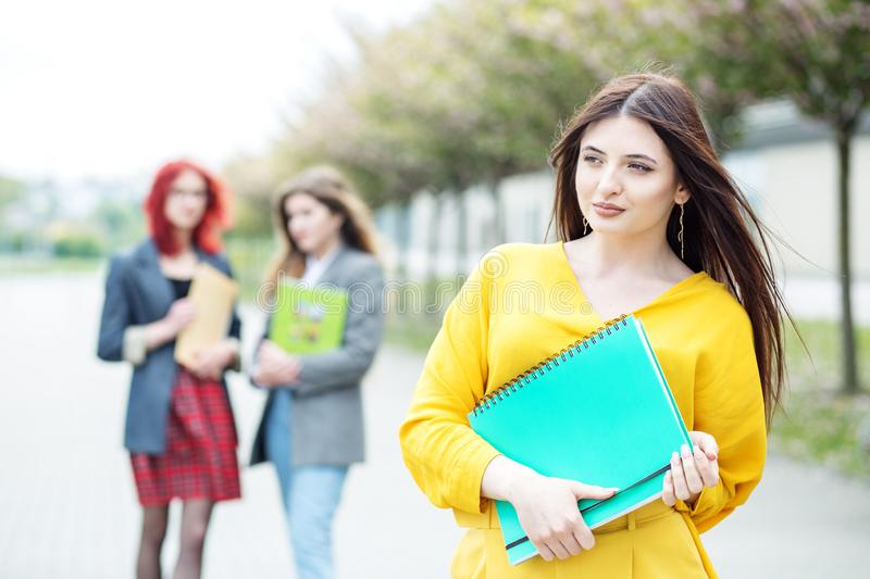 Beautiful girl student standing with a folder. Education concept, exams, friendship and group of people stock images