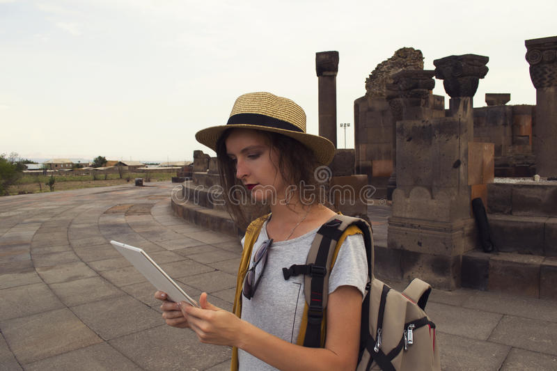 Beautiful girl student using tablet for distance education during traveling. Mobility, technology and travel concept. royalty free stock image