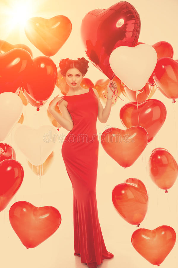 Beautiful girl, stylish fashion model with balloons in the shape. Of a heart. Woman on Valentine`s Day. Symbol of love royalty free stock photography