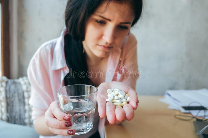 A beautiful girl suffering from pain, not a healthy business woman holding a pill and a stack of water. Student teenager drinking royalty free stock image