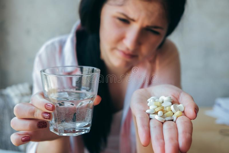 A beautiful girl suffering from pain, not a healthy business woman holding a pill and a stack of water. Student teenager drinking royalty free stock images