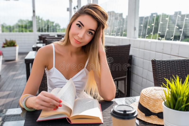 Beautiful girl in summer cafe. Reads paper book, art detective. On table is cup of coffee or tea, and a straw hat. Beautiful girl in summer cafe. Reads paper stock images