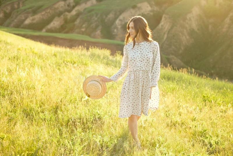 Beautiful girl in a summer sundress walks through the mountains in her hands holding a straw hat enjoying the rays of stock images