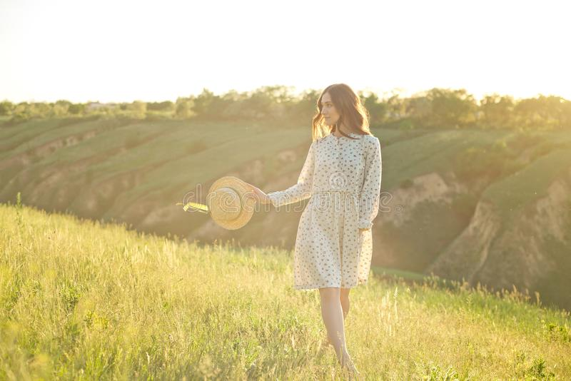 Beautiful girl in a summer sundress walks through the mountains in her hands holding a straw hat enjoying the rays of stock photography