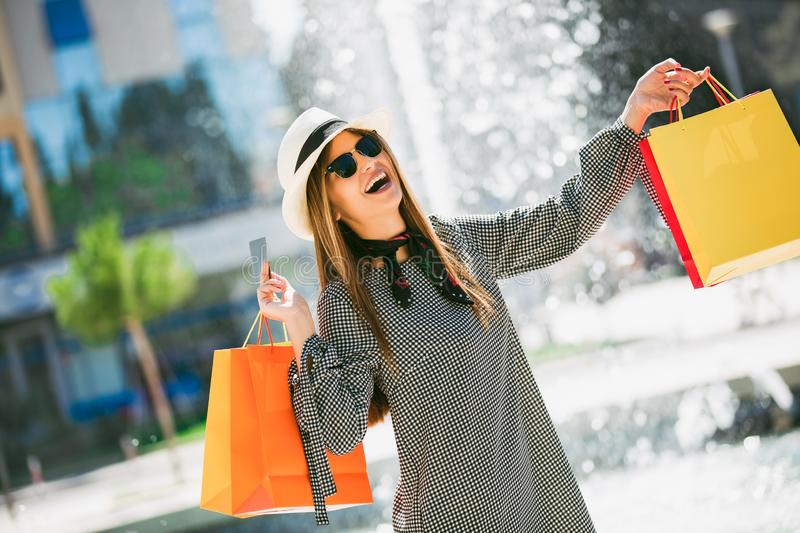 Beautiful girl in sun glasses holding shopping bags and credit card and smiling stock photography