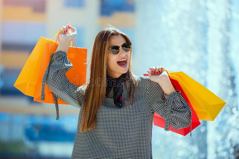 Beautiful girl in sun glasses is holding shopping bags and smiling stock photos