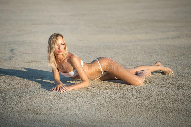 Beautiful girl sunbathing at the beach in white swimsuit. Sand b royalty free stock photos