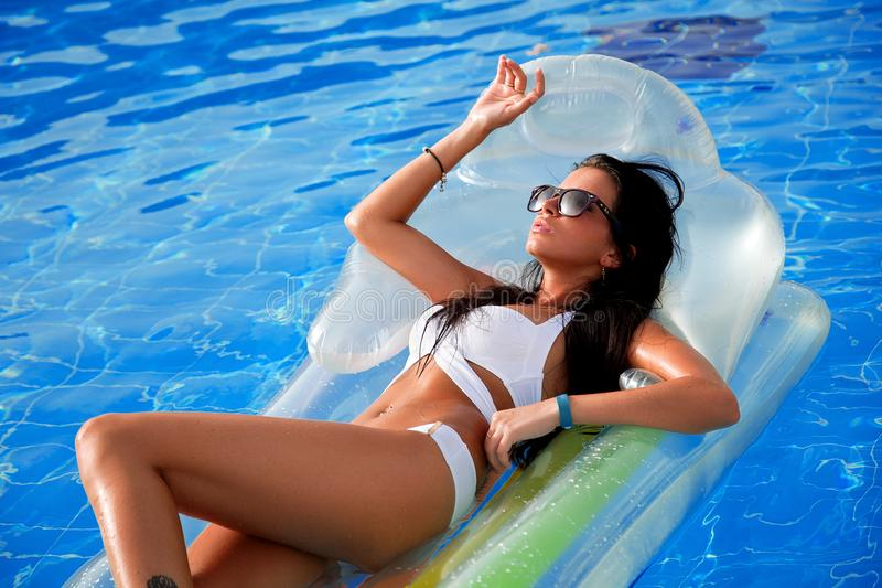Beautiful girl sunbathing in the pool on an inflatable mattress royalty free stock photos